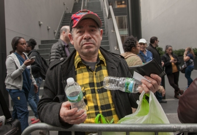 Custodial Assistant Raymond Luciano holds bottles, which he plans to recycle to supplement his frozen pay. He earns about $150 every two weeks by recycling.